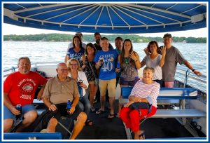 A group of people, of various ages, enjoying a Lake of the Ozarks Party Boat Charter aboard a Playin Hooky boat.